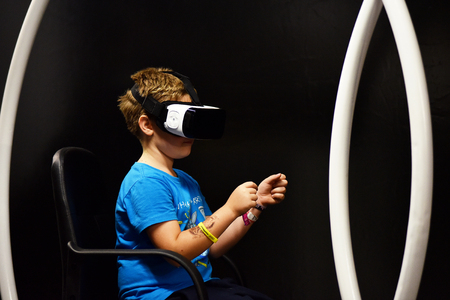 CLUJ-NAPOCA, ROMANIA - AUGUST 5, 2016: Boy tries virtual reality Samsung Gear VR headset and hand controls during the virtual reality exposition, at the Untold Festival Editorial