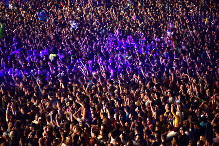 clubbers: CLUJ NAPOCA, ROMANIA - JULY 8, 2016: Crowd having fun with raising hands at a Lost Frequencies live concert at Untold Festival, the Best Major Music Festival of Europe