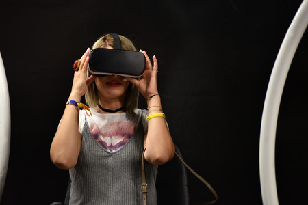 CLUJ-NAPOCA, ROMANIA - AUGUST 7, 2016: Girl tries virtual reality Samsung Gear VR headset and hand controls during the virtual reality exposition, at the Untold Festival