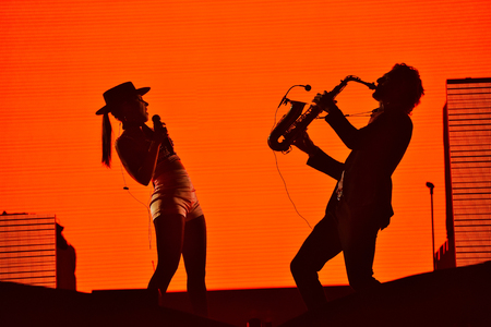 soloist: CLUJ-NAPOCA, ROMANIA - AUGUST 7, 2016: Silhouette of singer Cleo Panther (left) and saxophone player from Parov Stelar Band performing live on the stage at Untold Festival
