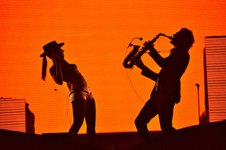 festival moments: CLUJ-NAPOCA, ROMANIA - AUGUST 7, 2016: Silhouette of singer Cleo Panther (left) and saxophone player from Parov Stelar Band performing live on the stage at Untold Festival