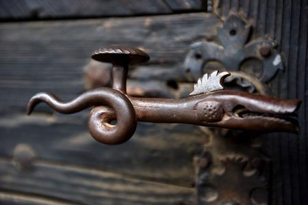 Ornamental vintage iron door handle on a wooden door Stock Photo
