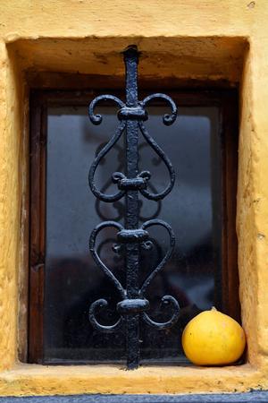 iron barred: Ornamental forged metal lattice on a basement window. Ornamental yellow pumpkin Stock Photo