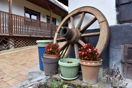 old wood farm wagon: Weathered vintage wooden wheel in a rural yard as a decoration Stock Photo