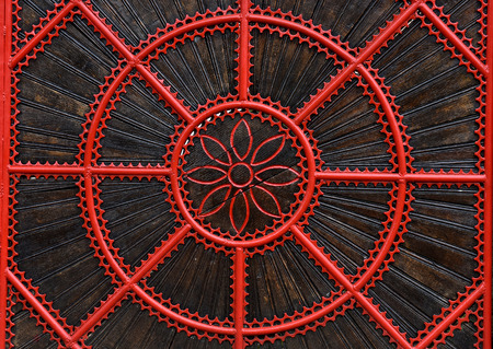 Detail of a red forged metallic gate. Forged decorative fence