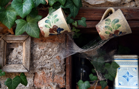 stoop: Vintage ceramic cups hanging in a cupboard