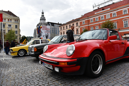 CLUJ-NAPOCA, ROMANIA - OCTOBER 15, 2016: Red Porsche and other vintage cars exhibited during the Retro Mobile Autumn Parade in the city of Cluj Napoca. Event organized by Retro Mobil Club Romania