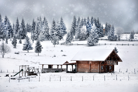 snowbank: Christmas greetings background. Small wooden cottage and fir trees. Stock Photo