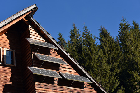 conserving: Solar panel on a wooden cottage in the forest