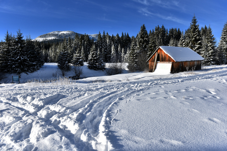 ski lodge: Idyllic winter mountain landscape with a wooden chalet Stock Photo