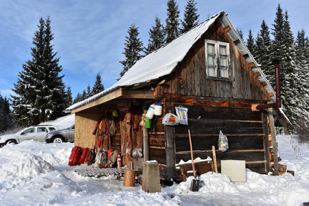 PADIS, ROMANIA - DECEMBER 4, 2016: Spelunkers drying their cave equipment hanged on a wooden cabin in the snow covered forest in a bright sunny day Editorial