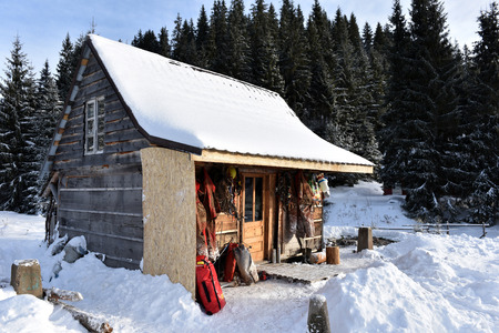 descender: PADIS, ROMANIA - DECEMBER 4, 2016: Spelunkers drying their cave equipment hanged on a wooden cabin in the snow covered forest in a bright sunny day Editorial