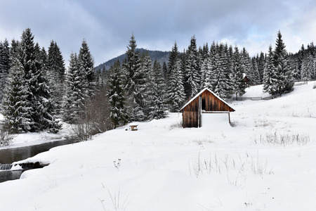Alpine house covered with snow in the mountains at winter Stock Photo