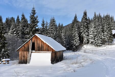 ski lodge: Alpine house covered with snow in the mountains at winter Stock Photo