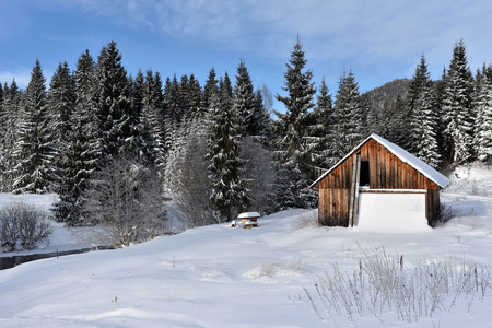 Winter landscape with a small wooden lodge in the mountains Stock Photo