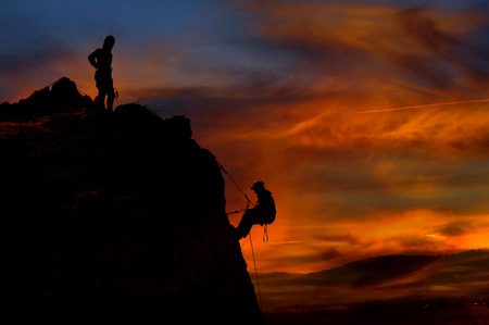 Climber waiting his partner on the summit. Beautiful sunset landscape in the background