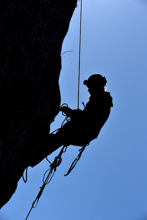 rappel: Silhouette of a rock climber hanging on the wall in the way to the summit