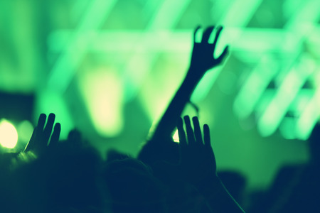 Rear view of crowd with arms outstretched at concert Stock Photo