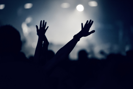Crowd at a music concert with raising hands up, toned image Stock Photo