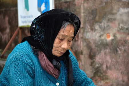 NINH BINH,VIETNAM - FEBRUARY 21, 2013: Elderly Vietnamese woman with a scarf living in the rural areas of Ninh Binh, Vietnam