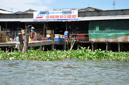 overpopulated: CAN THO, VIETNAM - FEBRUARY 17, 2013: Typical shack homes, riverside stils houses along the Mekong Delta. People from the suburbs are living in poverty with a low standard of living Editorial
