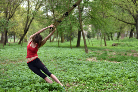 Young attractive woman does body stretching with trx fitness straps in the outdoors