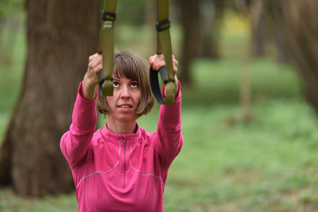 Woman doing arms biceps curl training with trx fitness straps in the outdoors Stock Photo