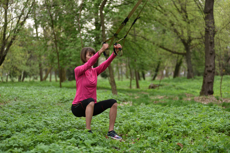 jungle gyms: Beautiful young woman doing TRX exercise with suspension trainer sling in the outdoors. Healthy lifestyle concept