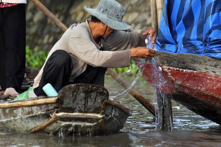 CAN THO, VIETNAM - FEBRUARY 17, 2013: Fisherman fishing with fishing nest in the Mekong delta, Vietnam. Mekong delta is one of the biggest wetland in the world