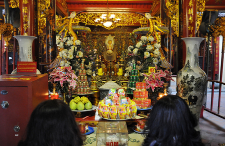 HANOI, VIETNAM - FEBRUARY 19, 2013: Sacrifice oblation, traditional offerings for Gods, bundles of money for spirits and fruits brought by Vietnamese pilgrims in Bach Ma temple, Hanoi