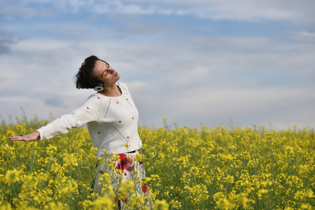 mp3 player: Beautiful Caucasian girl listening to music from her cell phone in a yellow canola field Stock Photo