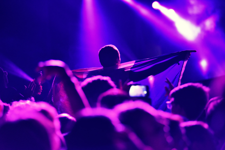 Silhouette of hands on a concert in front of bright stage lights Stock Photo