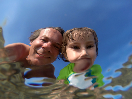 Father and her toddler daughter having fun at the sea. Distorted faces view through water, underwater view