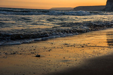 water wave: Waves approaching sandy beach during golden sunset Stock Photo