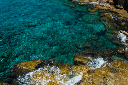 water wave: Crystal clear turquoise sea water background and rocky coast, shoreline