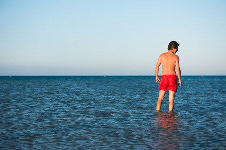 Slanke kerel poseren in rode badkleding in zeewater. Parodie concept