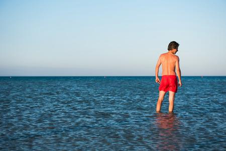 Slim guy posing in red swimwear in sea water. Parody concept Stock Photo