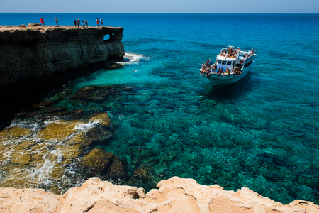 AYIA NAPA, CYPRUS, JUNE 15, 2017: Tourist boat approaching the sea caves of Ayia Napa from the sea. The littoral caves are one of the major tourist attractions of the island of Cyprus Editorial