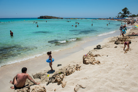 NISSI BEACH, AYIA NAPA, CYPRUS - JUNE 15, 2017: Tourists relaxing on the beach in the summer vacation. Nissi beach Cyprus most famous beach with white sand Editorial