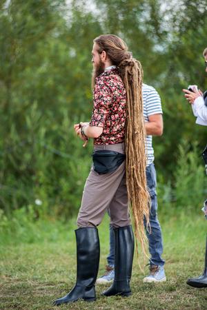 BONTIDA, ROMANIA - JULY 16, 2017: Young blonde man with long rasta dreadlocks and black horseriding boots enjoying Electric Castle festival