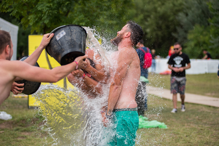 BONTIDA, ROMANIA - JULY 16, 2017: Funny guy spours water from a bucket on his friend head at Electric Castle Festival