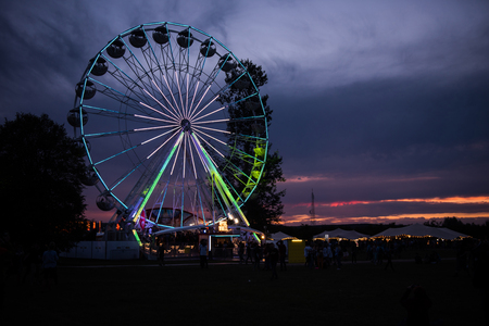 14: BONTIDA, ROMANIA - JULY 14, 2017: People of Electric Castle festival enjoying a ride at night on the Giant ferris wheel