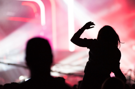 dancing club: Rear view of silhouette of crowd with arms outstretched at concert. Summer music festival concept