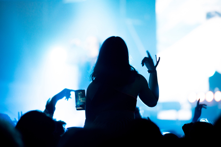 dancing club: Rear view of crowd with arms outstretched at concert. Bright stage lights in the background