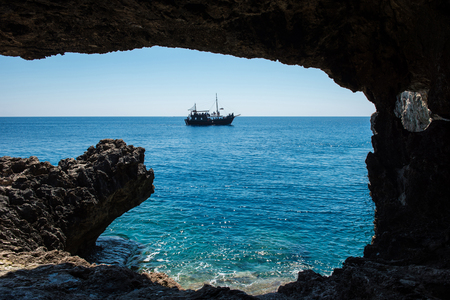 Pirate ship sailing in the sea. View from inside a cave
