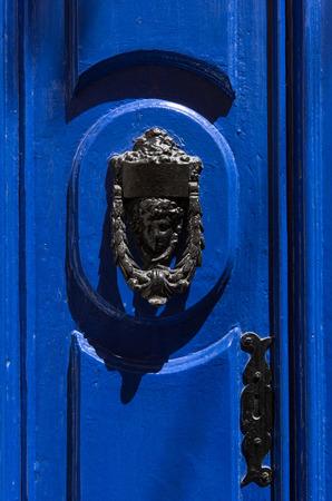 door handle: Decorative bronze door handle in the form of a beautiful womans head on a blue painted door. Malta
