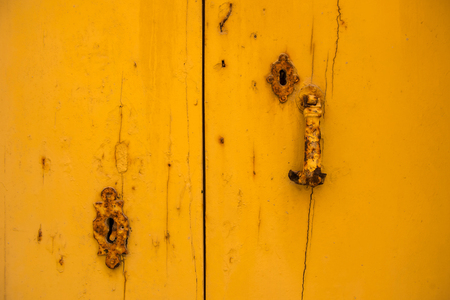 Rusty vintage keyhole on a yellow wooden door Stock Photo