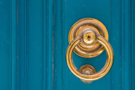 Golden door knocker on a blue wooden door. Mdina, Malta