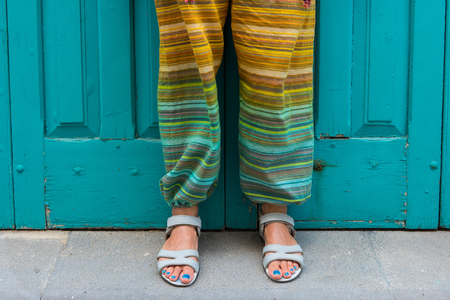 Feet of a woman in sandals with blue toe nails. Colorful hippie pants. Detail Banco de Imagens