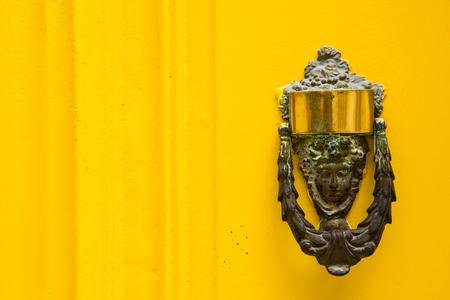 door handle: Decorative bronze door handle in the form of a beautiful womans head on a yellow painted door. Malta